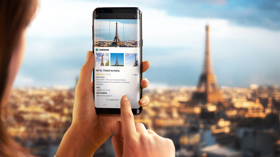 someone using Bixby on their smartphone's camera to view and get info on the Eiffel Tower