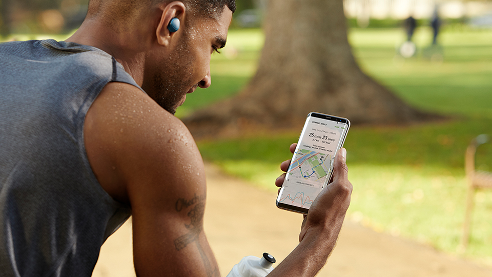 man checking his running route on a Samsung smartphone during his jog