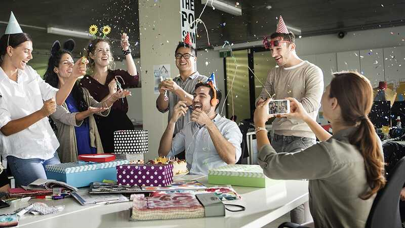 People celebrating in an office taking a group photo on a smartphone