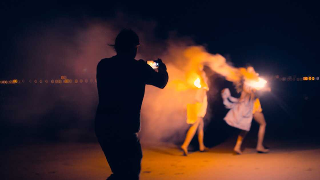 A man taking a photograph of two women with sparklers