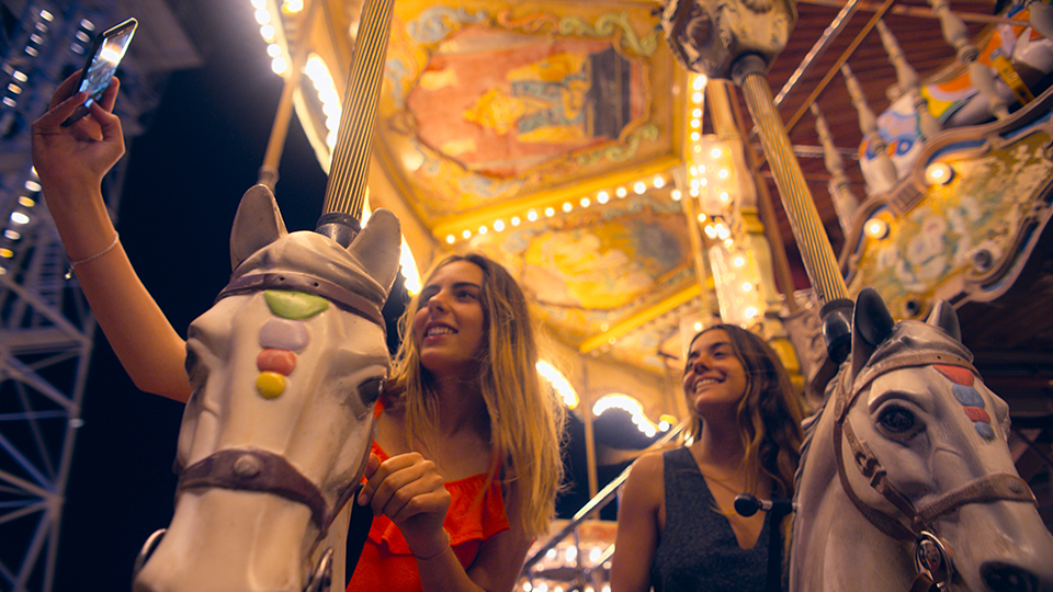 two girls taking a selfie on a carousel