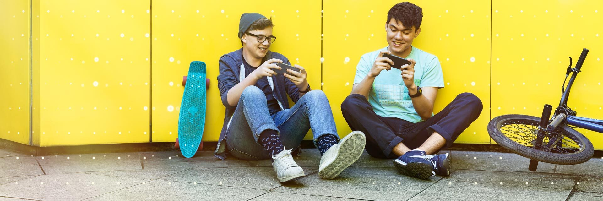 Two students playing a game on their smartphones