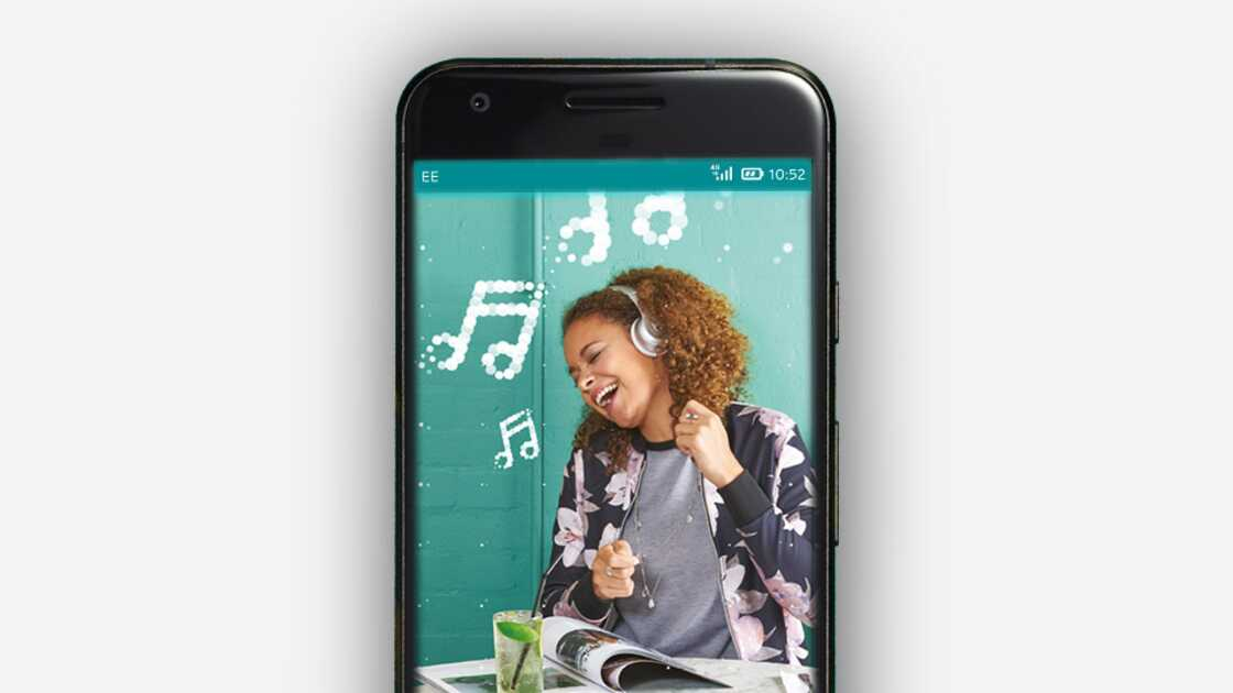Phone screen displaying a woman singing along to music coming out of her headphones