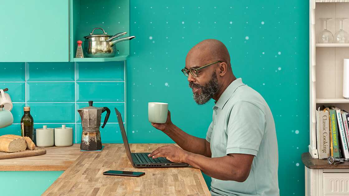 Man sitting in his kitchen, drinking tea and using his laptop