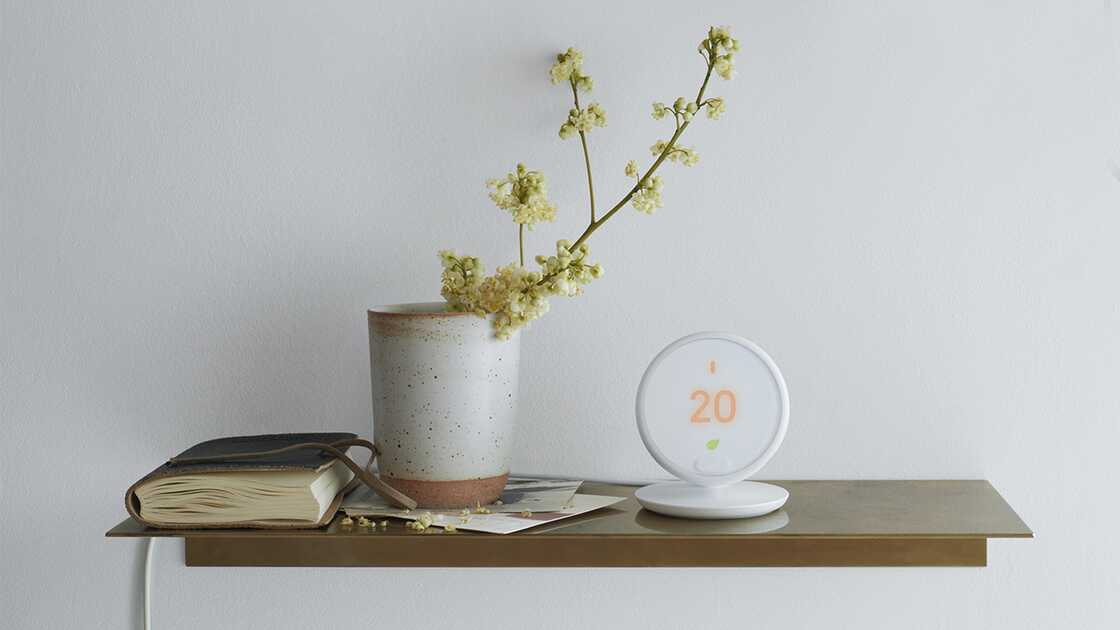 The Google Nest Learning Thermostat on a table next to a book and a plant.