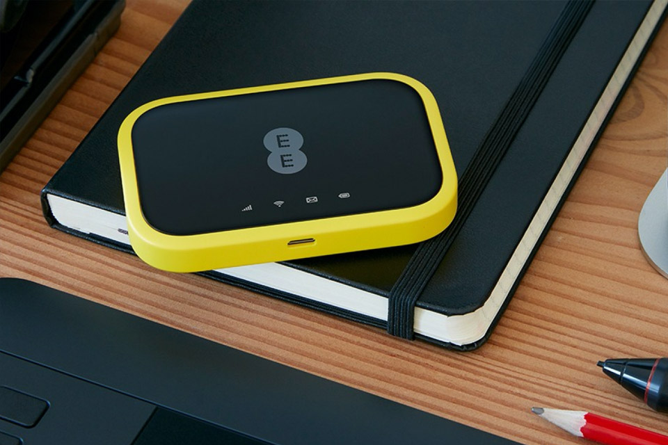 A black and yellow mini EE WiFi dongle.
