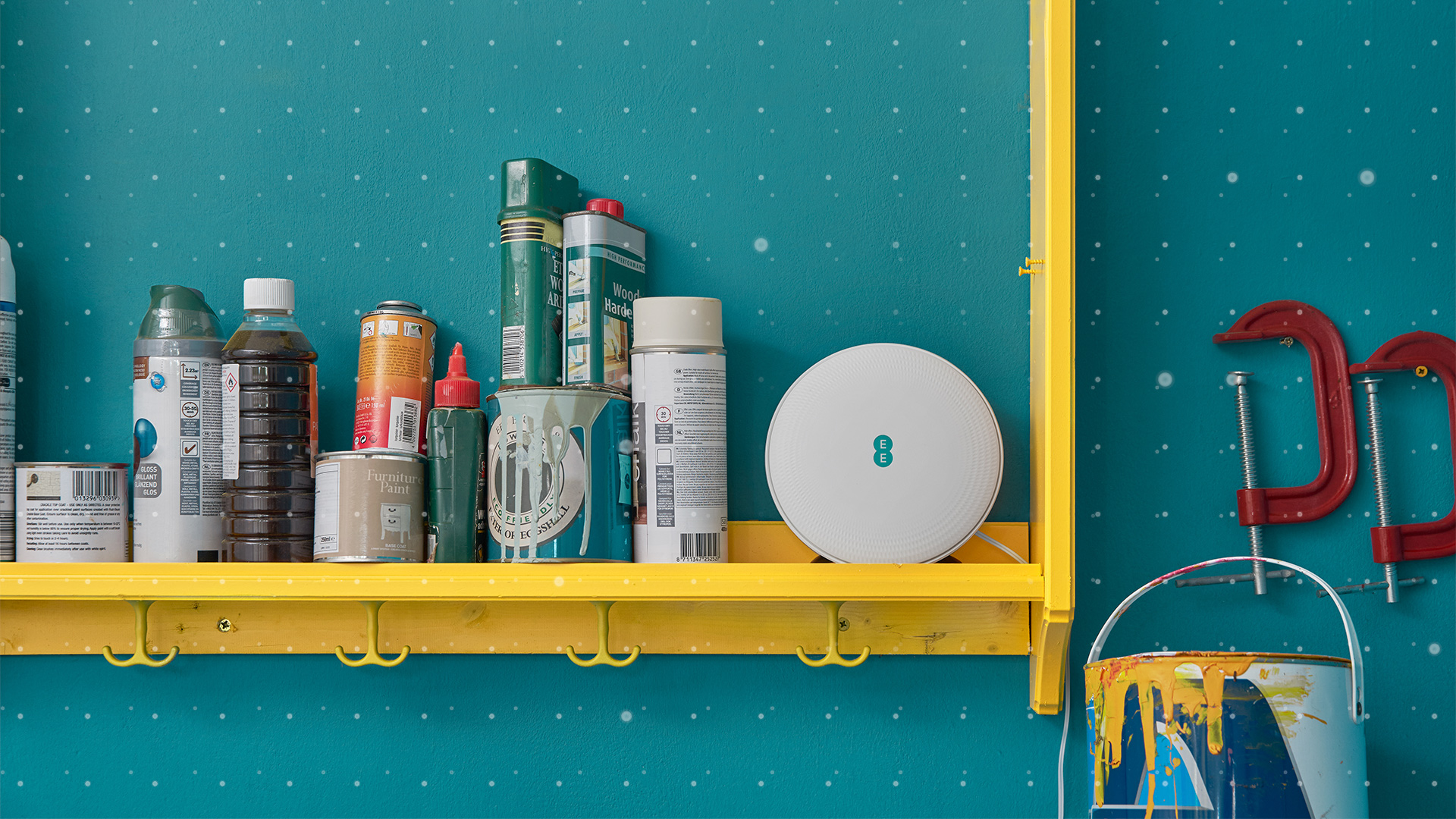 EE Smart WiFi booster disc postioned on shelf next to paints and home decorating products