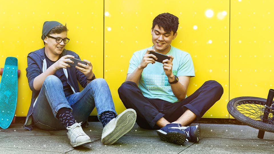 two friends playing games on their phones