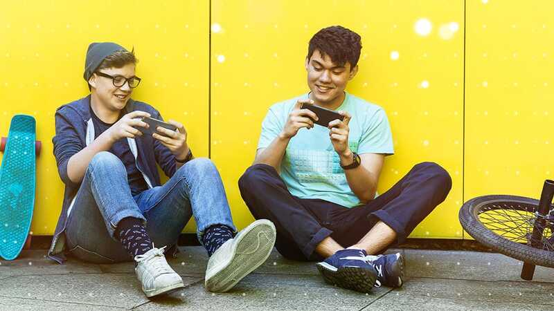 Two young men sat down playing games on their smartphones