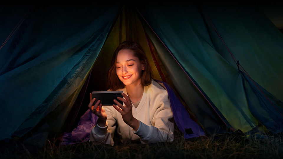 A woman in a tent looking at her Oppo Find X2 Neo 5G