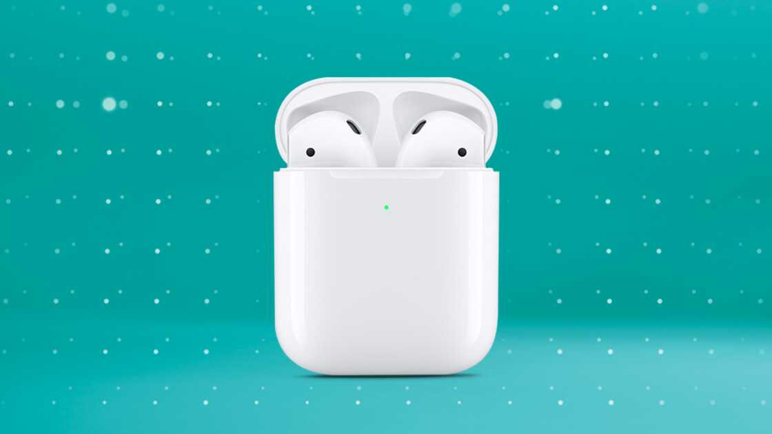 Apple AirPods in charging case on a green background