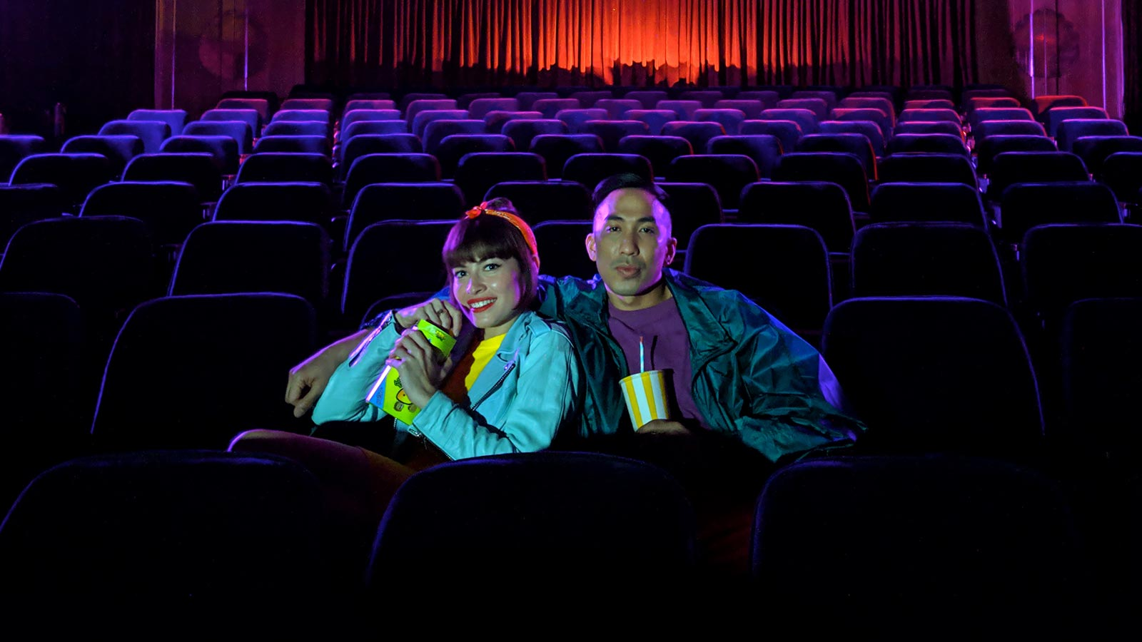 Woman and man sitting looking relaxed in a dark room surrounded by rows of seats