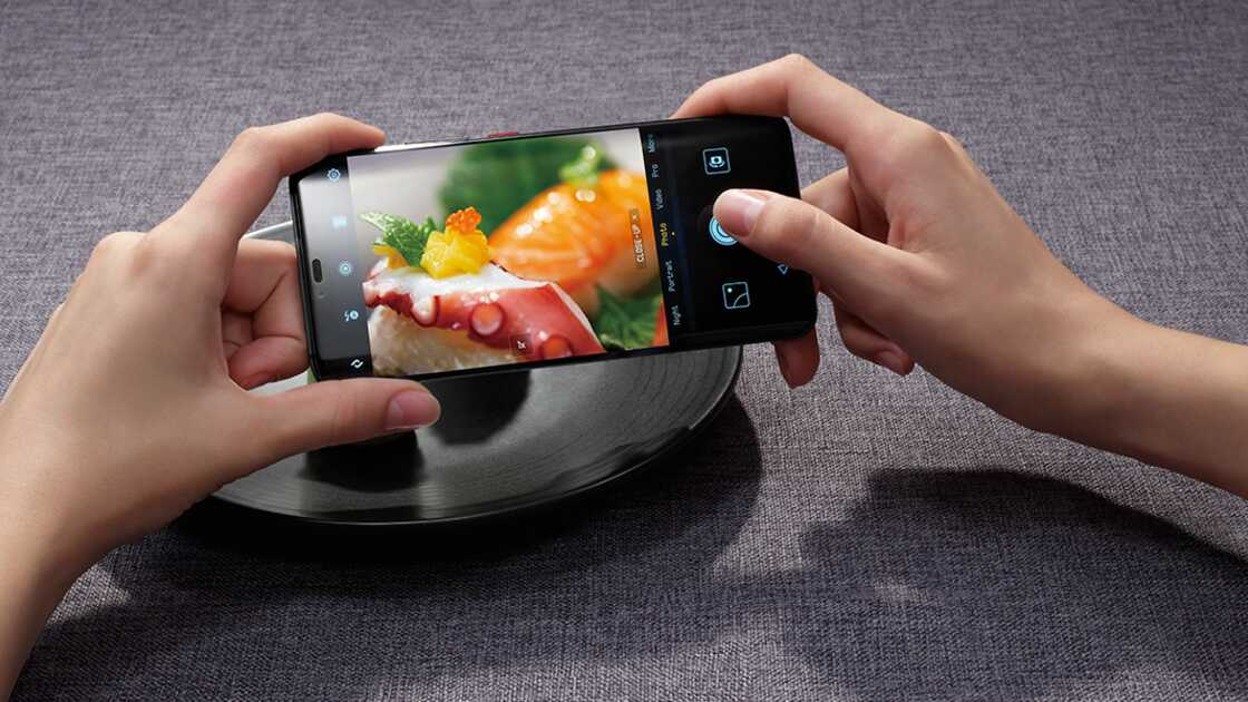 A person taking a photograph of sushi on a black plate with a Huawei Mate 20 Pro, against a grey background.