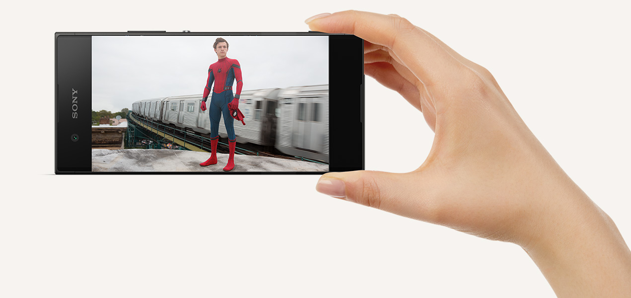 A hand holding the Sony Xperia XA1 showing a film