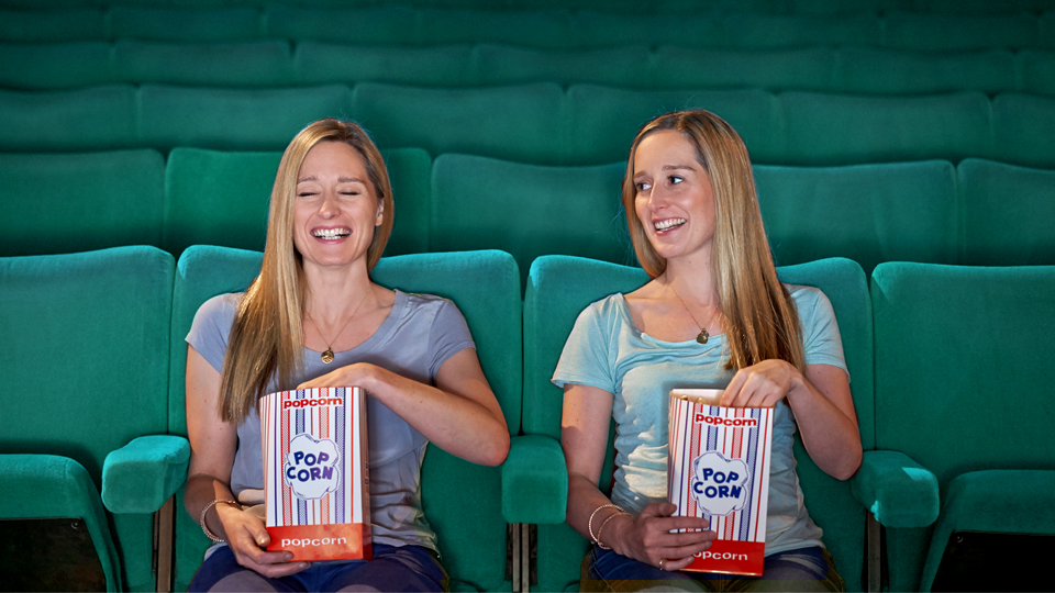 two women at the cinema eating popcorn