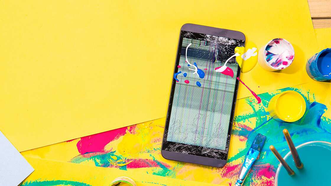 Mobile phone with damaged screen splashed with paint