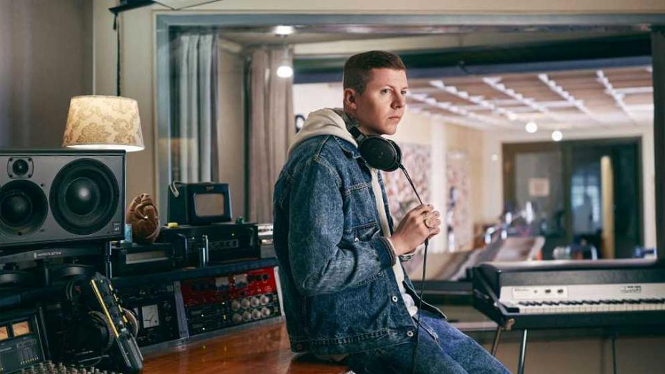 Professor Green sitting in a recording studio with headphones on