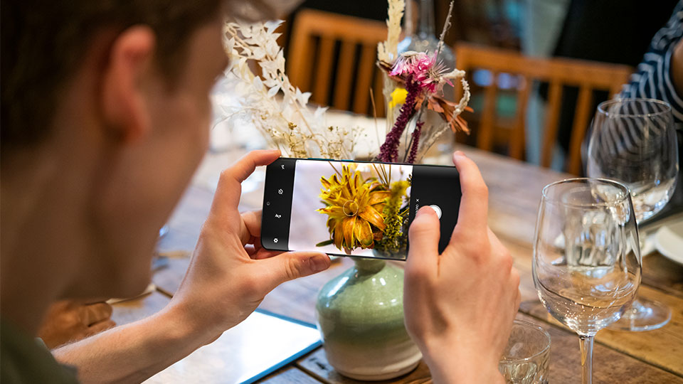 someone taking a photo of flowers on a table on their TCL 10 Pro