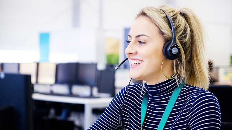 EE call centre employee smiling on the phone