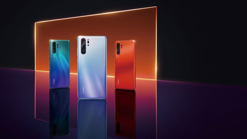 Huawei P30 smartphones on an orange and black background
