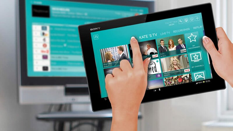 Person touching tablet with EE TV app on screen with TV in background showing EE TV