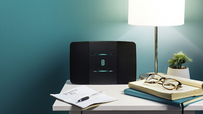 Black EE router on white shelf on aqua wall