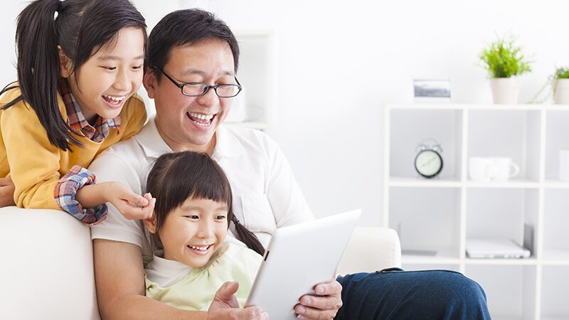Dad and two children looking at a tablet screen