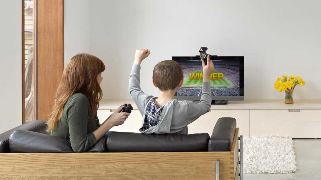 Two people playing game on TV