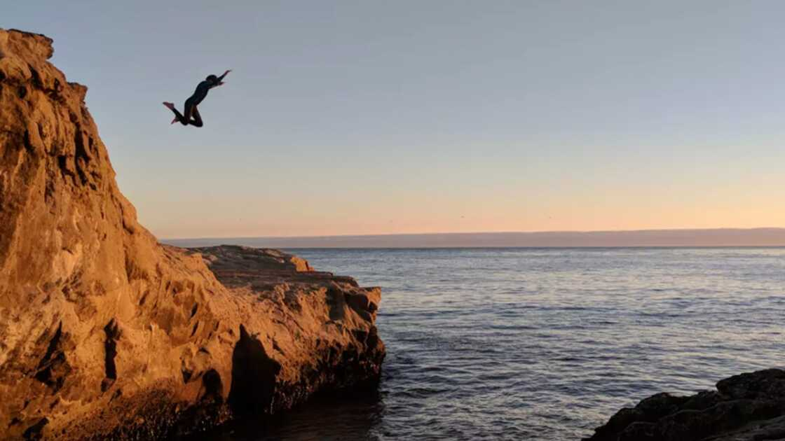 Woman jumping off a cliff face into the sea