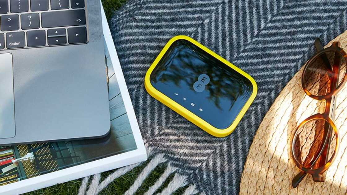 EE yellow 4GEE WiFi device on picnic blanket next to a laptop, sunglasses and a sun hat
