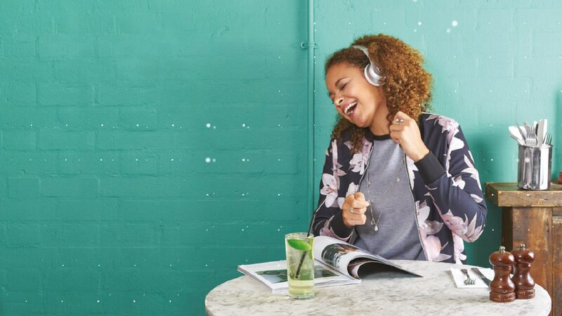 Lady sitting at a kitchen table listening to music wearing iPhone headphones