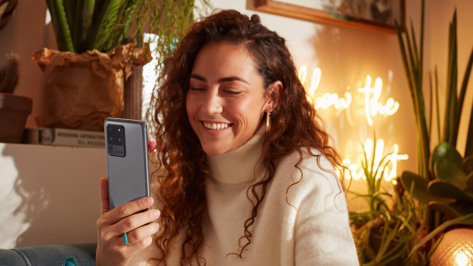 a woman with curly brown hair looking at her Galaxy S20 Ultra 5G while smiling and sitting in a cosy indoor setting