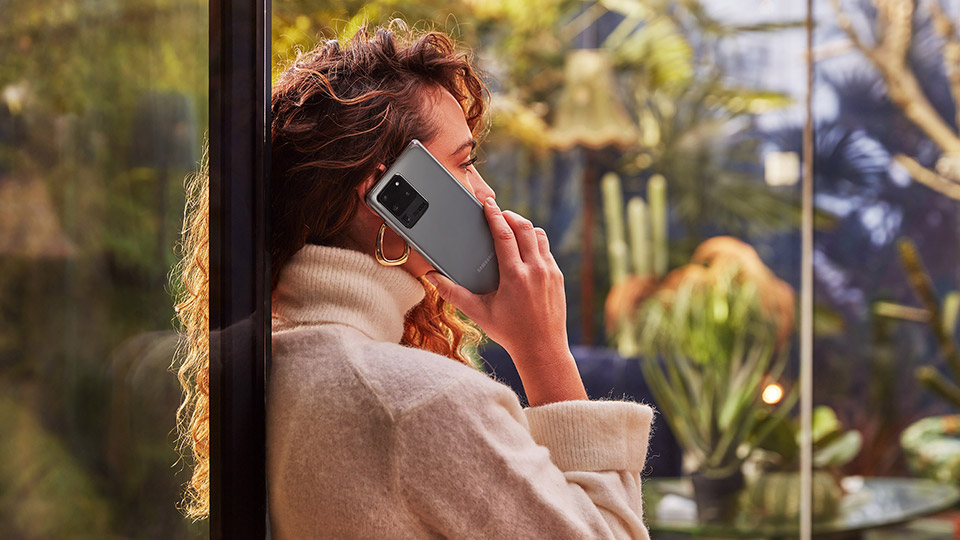 a woman with brown curly hair stood by the window talking on her samsung galaxy s20 ultra 5g while looking outdoors